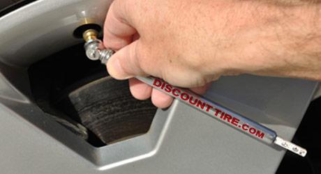 Using a standard tire pressure gauge to check tire air pressure